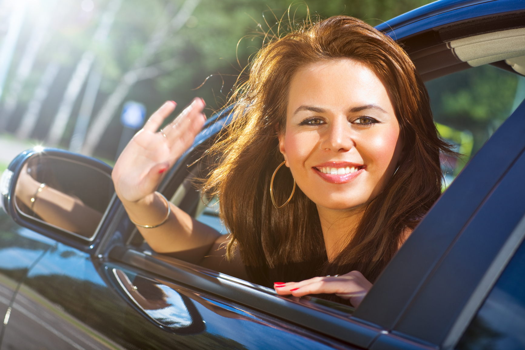 Young woman looking out of car and waving hand.