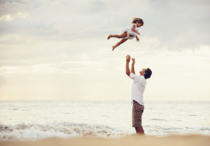Healthy loving father and daughter playing together at the beach